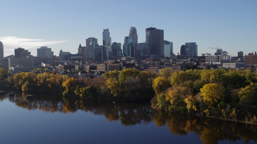 5.7K stock footage aerial video reverse view of skyline of Downtown Minneapolis, Minnesota, seen from river, reveal bridge Aerial Stock Footage | DX0001_002341