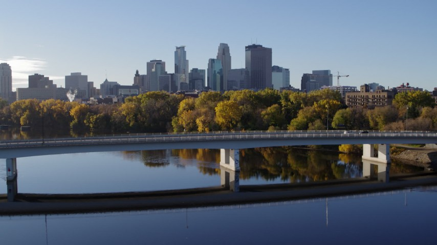 5.7K stock footage aerial video flyby a bridge spanning river with a view of the skyline of Downtown Minneapolis, Minnesota Aerial Stock Footage | DX0001_002352