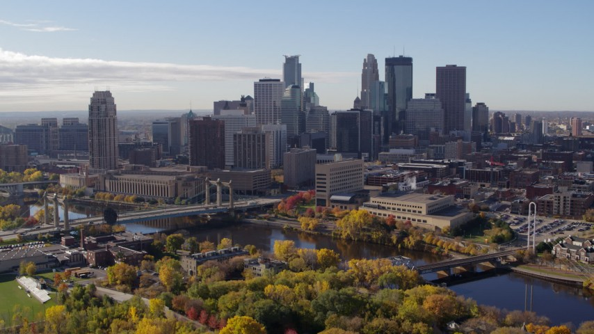 5.7K stock footage aerial video flying by bridges spanning the river and the city skyline, Downtown Minneapolis, Minnesota Aerial Stock Footage | DX0001_002355