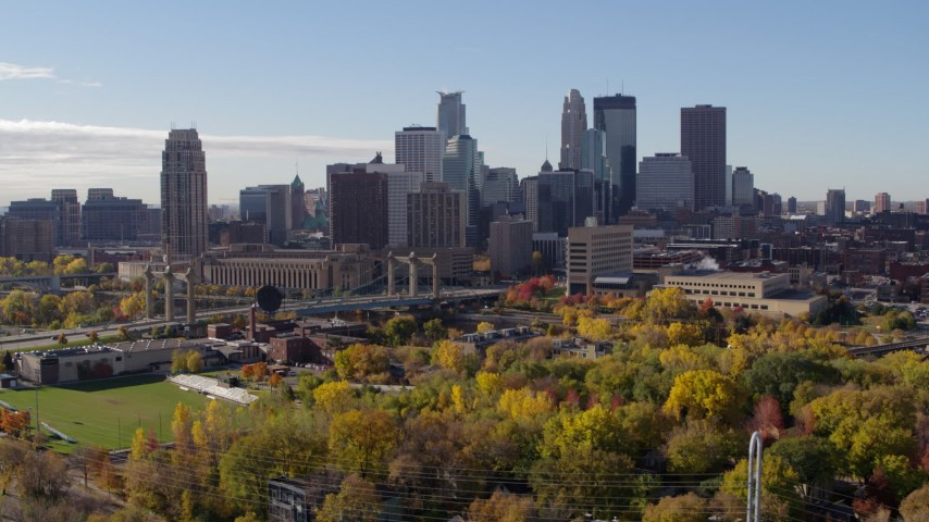 5.7K stock footage aerial video ascend from trees to flyby the city's skyline across the river, Downtown Minneapolis, Minnesota Aerial Stock Footage | DX0001_002358
