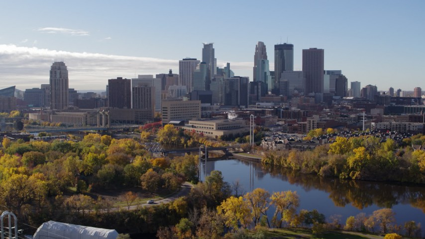 5.7K stock footage aerial video ascend from trees to flyby the city's skyline, reveal the river, Downtown Minneapolis, Minnesota Aerial Stock Footage | DX0001_002360