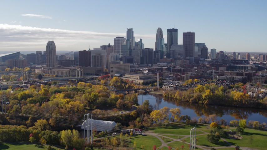 5.7K stock footage aerial video flying by the city's skyline across the river, seen from a park, Downtown Minneapolis, Minnesota Aerial Stock Footage | DX0001_002363