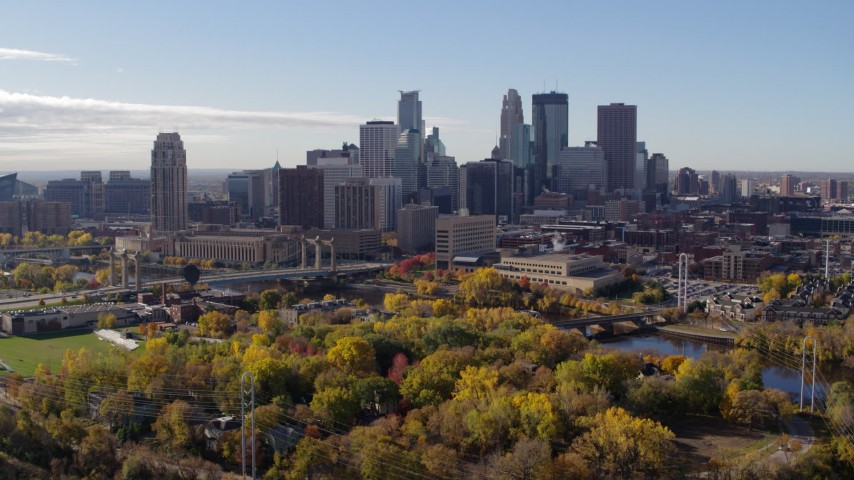 5.7K stock footage aerial video approach the city's skyline across the river, seen from a park, Downtown Minneapolis, Minnesota Aerial Stock Footage | DX0001_002364