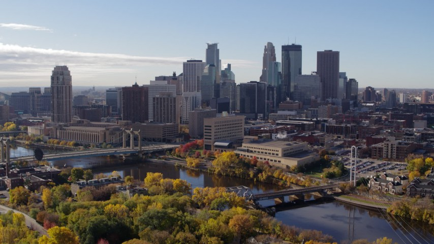 5.7K stock footage aerial video approach the city's skyline and bridges spanning the river, seen from a park, Downtown Minneapolis, Minnesota Aerial Stock Footage | DX0001_002365