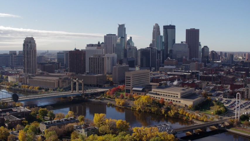5.7K stock footage aerial video flying by the city's skyline and bridges spanning the river, Downtown Minneapolis, Minnesota Aerial Stock Footage | DX0001_002366