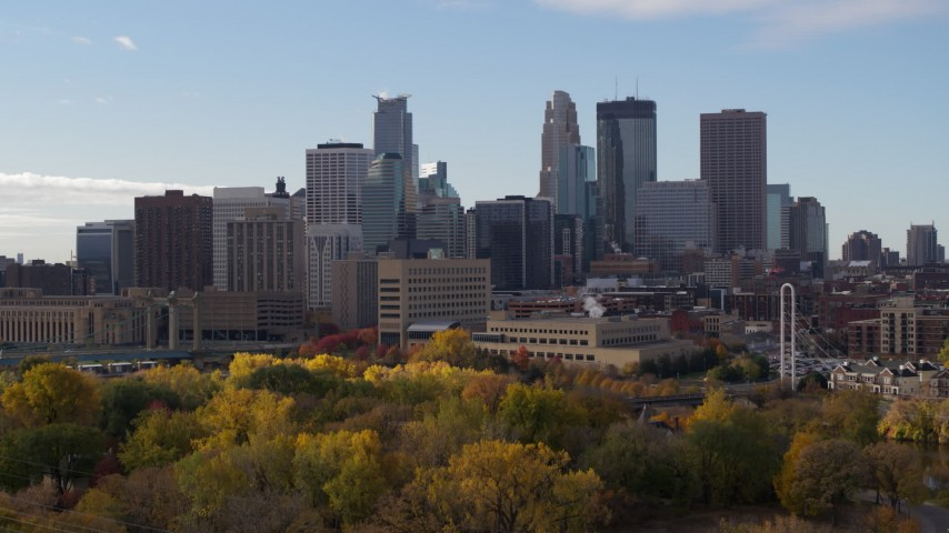 5.7K stock footage aerial video ascend from trees to reveal Mississippi River, focus on skyline of Downtown Minneapolis, Minnesota Aerial Stock Footage | DX0001_002368