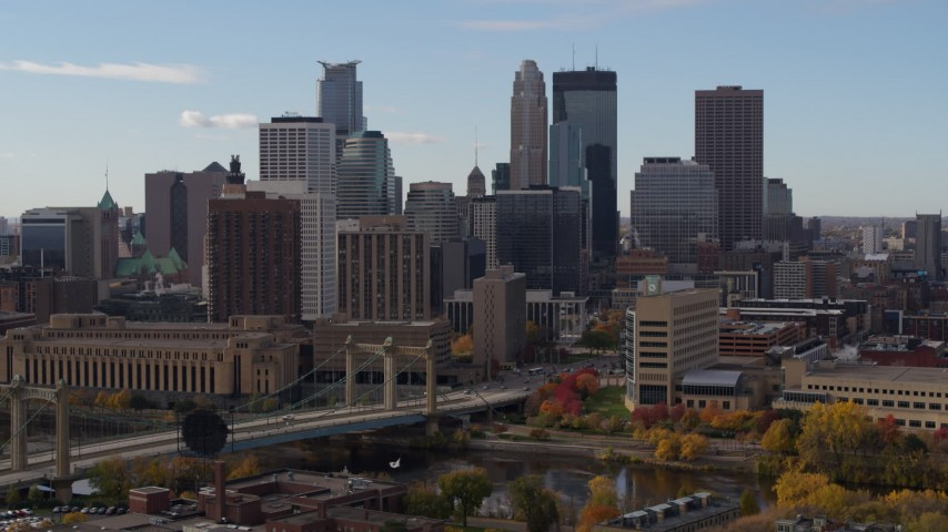 5.7K stock footage aerial video ascend near bridge and towering skyscrapers of the city skyline, Downtown Minneapolis, Minnesota Aerial Stock Footage | DX0001_002380