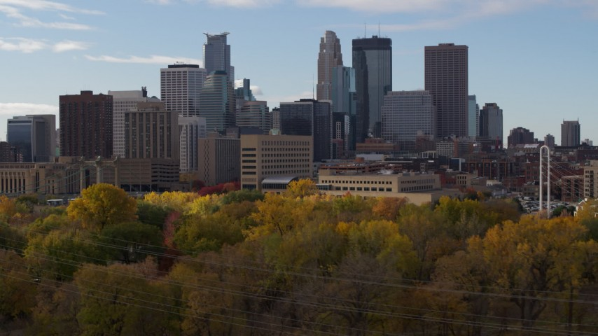5.7K stock footage aerial video descend near trees with view of towering skyscrapers of the city skyline, Downtown Minneapolis, Minnesota Aerial Stock Footage | DX0001_002382
