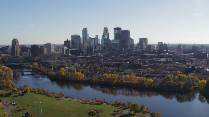 5.7K stock footage aerial video wide view of the city skyline, seen while flying by bridge spanning the river, Downtown Minneapolis, Minnesota Aerial Stock Footage | DX0001_002458