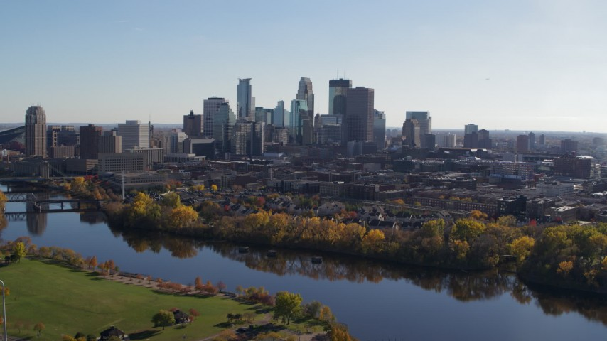 5.7K stock footage aerial video of the city skyline seen while flying by a bridge and the river, Downtown Minneapolis, Minnesota Aerial Stock Footage | DX0001_002464
