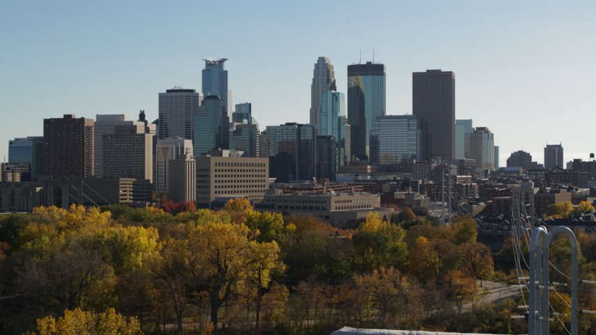 5.7K stock footage aerial video focus on the city skyline while descending by trees, Downtown Minneapolis, Minnesota Aerial Stock Footage | DX0001_002482