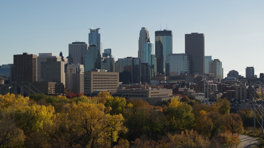 5.7K stock footage aerial video ascend over trees to focus on the city skyline, Downtown Minneapolis, Minnesota Aerial Stock Footage | DX0001_002483