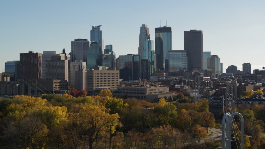 5.7K stock footage aerial video descend behind trees and focus on the city skyline, Downtown Minneapolis, Minnesota Aerial Stock Footage | DX0001_002484