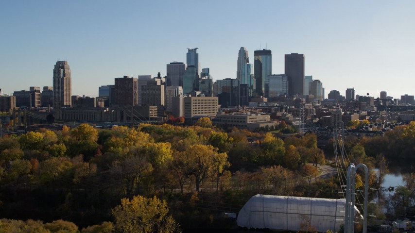 5.7K stock footage aerial video descend by trees and focus on the city skyline, Downtown Minneapolis, Minnesota Aerial Stock Footage | DX0001_002485