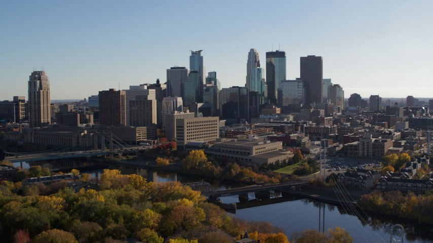 5.7K stock footage aerial video ascend over trees and approach the city skyline, Downtown Minneapolis, Minnesota Aerial Stock Footage | DX0001_002486