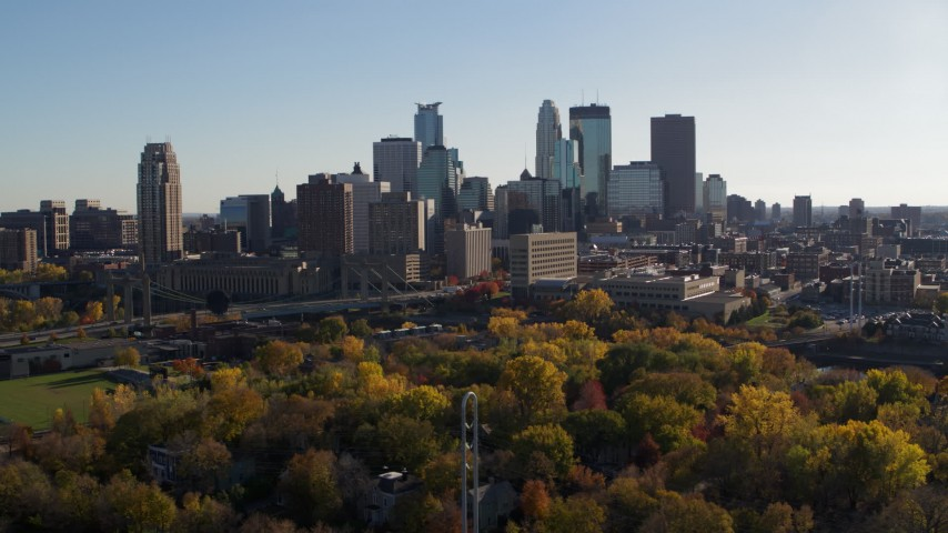 5.7K stock footage aerial video of flying by fall trees and the city skyline, Downtown Minneapolis, Minnesota Aerial Stock Footage | DX0001_002489