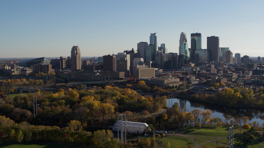 5.7K stock footage aerial video descend toward park with view of city skyline across the Mississippi River, Downtown Minneapolis, Minnesota Aerial Stock Footage | DX0001_002497