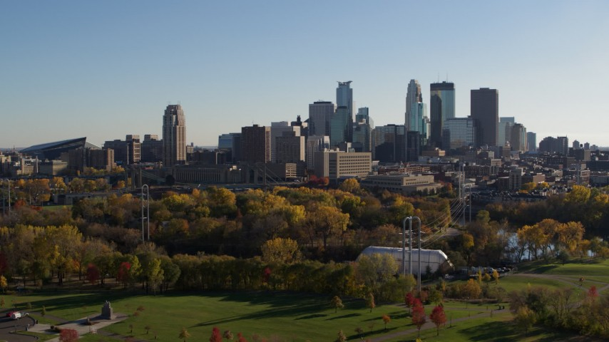 5.7K stock footage aerial video flying by park with view of city skyline across the Mississippi River, Downtown Minneapolis, Minnesota Aerial Stock Footage | DX0001_002498