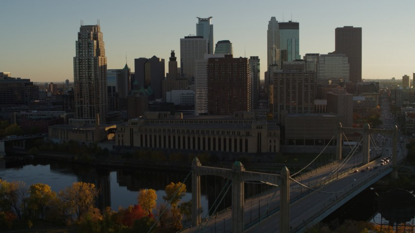 5.7K stock footage aerial video descend by Hennepin Avenue Bridge and apartment buildings at sunset in Downtown Minneapolis, Minnesota Aerial Stock Footage | DX0001_002505