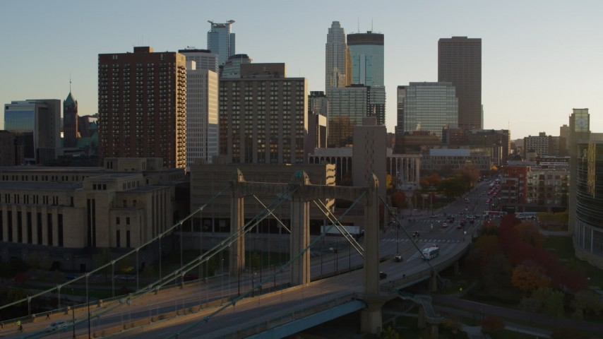 5.7K stock footage aerial video flyby and approach Hennepin Avenue Bridge at sunset near apartment buildings, Downtown Minneapolis, Minnesota Aerial Stock Footage | DX0001_002511
