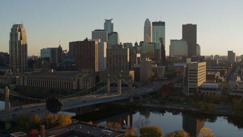 5.7K stock footage aerial video reverse view of Hennepin Avenue Bridge and city skyline at sunset, Downtown Minneapolis, Minnesota Aerial Stock Footage | DX0001_002514