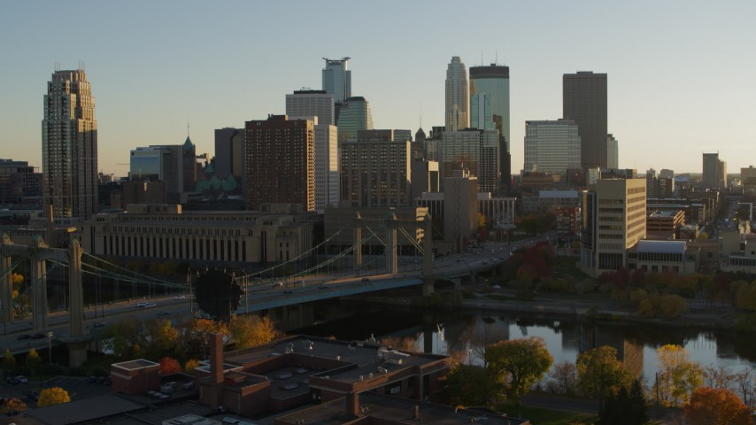 5.7K stock footage aerial video flying by Hennepin Avenue Bridge and city skyline at sunset, Downtown Minneapolis, Minnesota Aerial Stock Footage | DX0001_002515