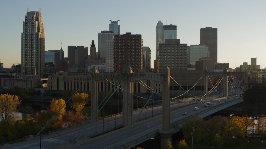 5.7K stock footage aerial video passing by Hennepin Avenue Bridge and city skyline at sunset, Downtown Minneapolis, Minnesota Aerial Stock Footage | DX0001_002516