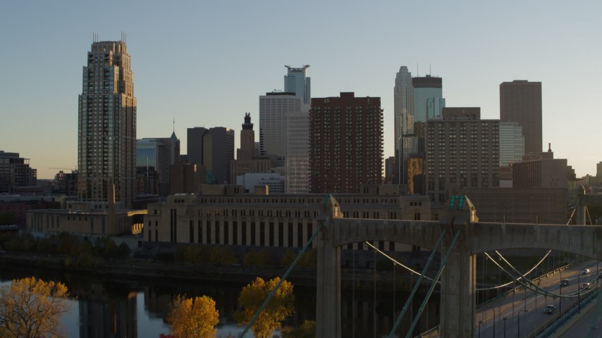 5.7K stock footage aerial video ascend by Hennepin Avenue Bridge, USPS and apartment buildings at sunset, Downtown Minneapolis, Minnesota Aerial Stock Footage | DX0001_002517