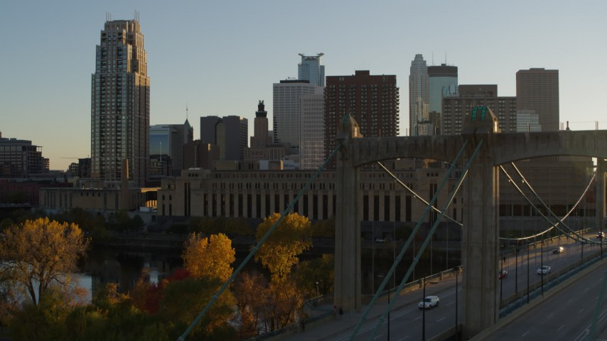5.7K stock footage aerial video descend by USPS and apartment buildings at sunset, reveal bridge in Downtown Minneapolis, Minnesota Aerial Stock Footage | DX0001_002518