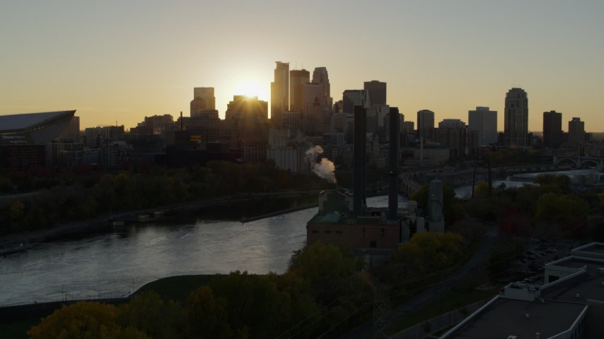 5.7K stock footage aerial video of the city skyline across the river and a power plant at sunset, Downtown Minneapolis, Minnesota Aerial Stock Footage | DX0001_002519