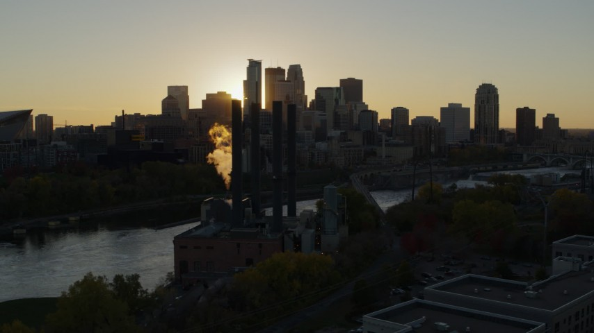 5.7K stock footage aerial video of the city skyline across the river while flying by a power plant at sunset, Downtown Minneapolis, Minnesota Aerial Stock Footage | DX0001_002520
