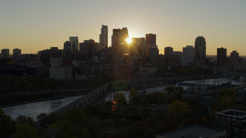 5.7K stock footage aerial video of the city skyline across the river while ascending at sunset, Downtown Minneapolis, Minnesota Aerial Stock Footage | DX0001_002521