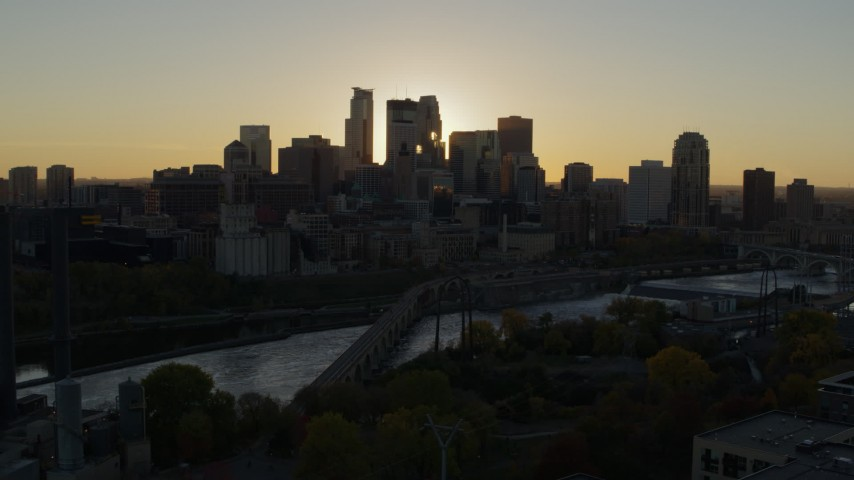 5.7K stock footage aerial video of flying by the city skyline across the river at sunset, reveal power plant, Downtown Minneapolis, Minnesota Aerial Stock Footage | DX0001_002522