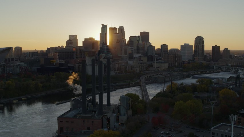5.7K stock footage aerial video of flying by power plant, with the city skyline across river at sunset, Downtown Minneapolis, Minnesota Aerial Stock Footage | DX0001_002523