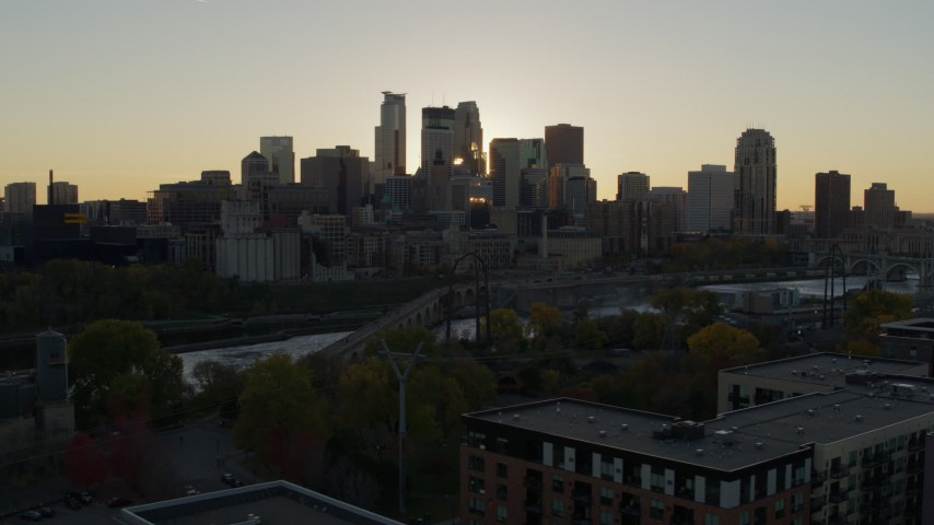 5.7K stock footage aerial video of flying by the city skyline across river at sunset, reveal power plant, Downtown Minneapolis, Minnesota Aerial Stock Footage | DX0001_002524