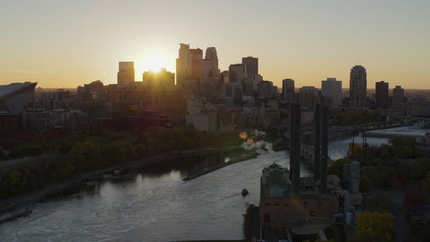 5.7K stock footage aerial video of flying by the power plant and river at sunset, focus on skyline, Downtown Minneapolis, Minnesota Aerial Stock Footage | DX0001_002525