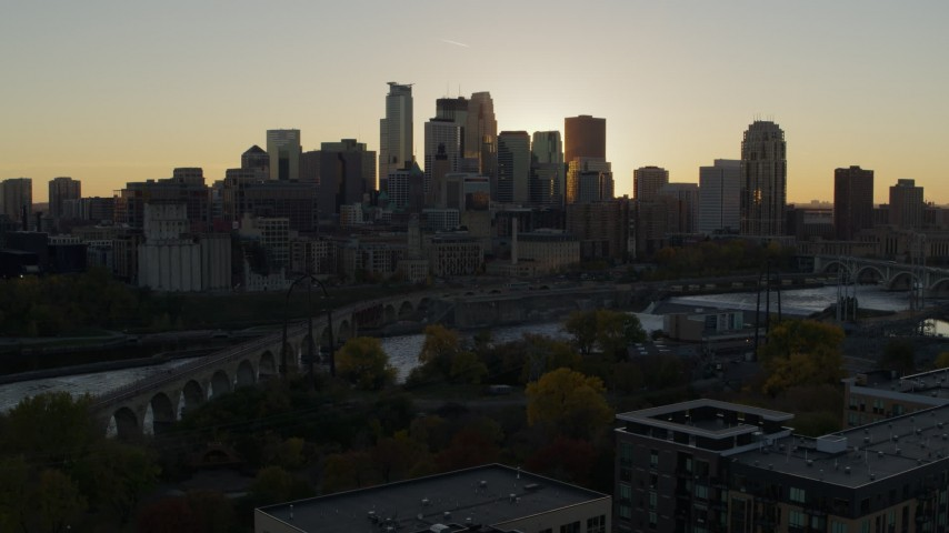 5.7K stock footage aerial video view of city skyline during descent by bridge and river at sunset, Downtown Minneapolis, Minnesota Aerial Stock Footage | DX0001_002528