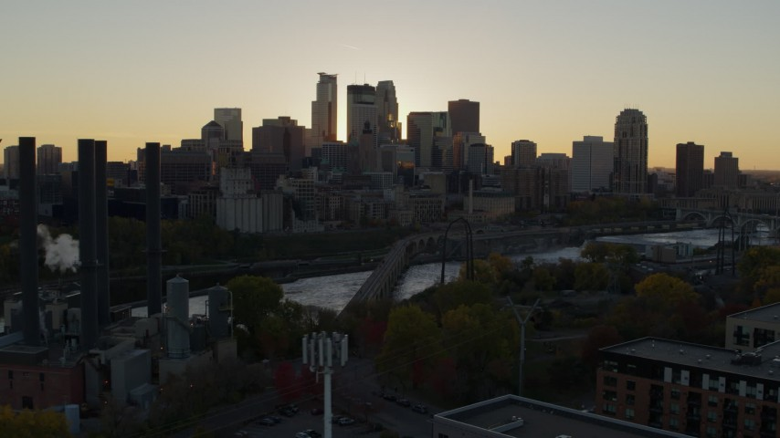 5.7K stock footage aerial video view of city skyline while flying by bridge and river at sunset, reveal power plant, Downtown Minneapolis, Minnesota Aerial Stock Footage | DX0001_002529