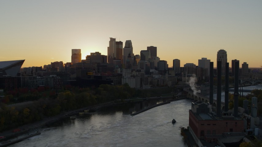 5.7K stock footage aerial video of city skyline across the Mississippi River at sunset, reveal power plant, Downtown Minneapolis, Minnesota Aerial Stock Footage | DX0001_002532