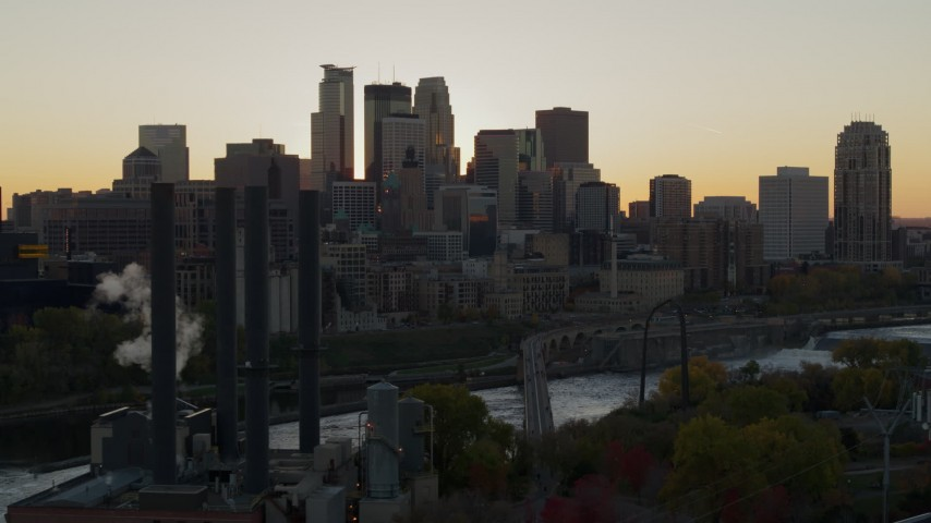 5.7K stock footage aerial video of city skyline across the Mississippi River at sunset, seen from power plant, Downtown Minneapolis, Minnesota Aerial Stock Footage | DX0001_002533