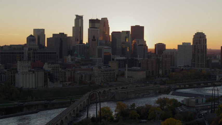 5.7K stock footage aerial video of city skyline across the Mississippi River at sunset, reveal power plant, Downtown Minneapolis, Minnesota Aerial Stock Footage | DX0001_002534