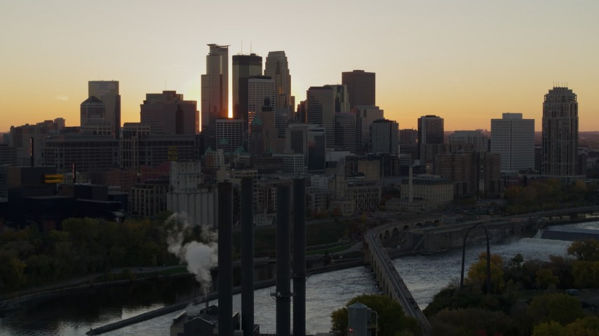 5.7K stock footage aerial video of city skyline across the Mississippi River at sunset, seen from the power plant, Downtown Minneapolis, Minnesota Aerial Stock Footage | DX0001_002535