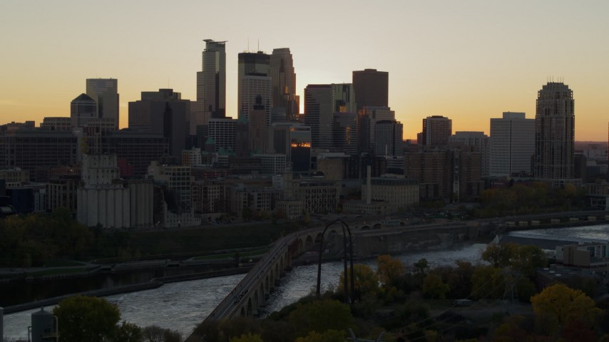 5.7K stock footage aerial video of city skyline across the Mississippi River at sunset, and reveal the power plant, Downtown Minneapolis, Minnesota Aerial Stock Footage | DX0001_002536