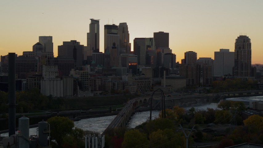 5.7K stock footage aerial video ascend to reveal river with view of city skyline in background at sunset, Downtown Minneapolis, Minnesota Aerial Stock Footage | DX0001_002538