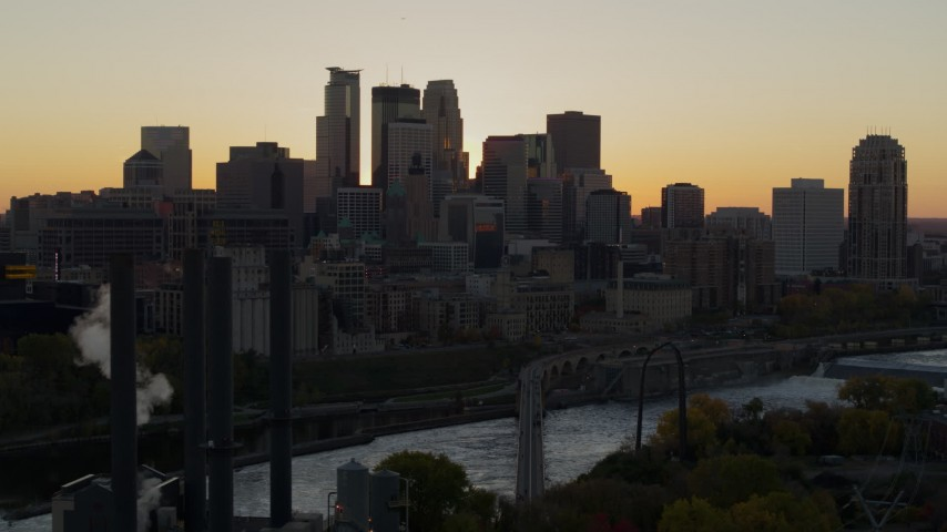 5.7K stock footage aerial video flyby river with view of city skyline in background at sunset, reveal power plant, Downtown Minneapolis, Minnesota Aerial Stock Footage | DX0001_002539