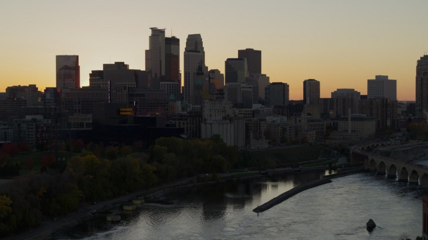 5.7K stock footage aerial video descend by river with view of city skyline in background at sunset, Downtown Minneapolis, Minnesota Aerial Stock Footage | DX0001_002540