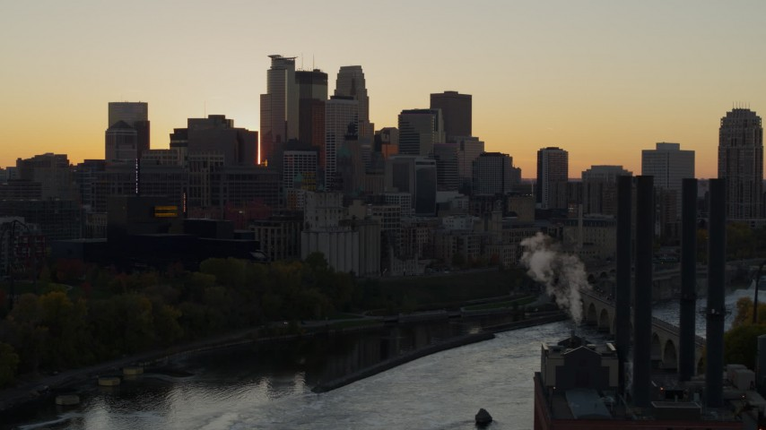 5.7K stock footage aerial video flyby river with view of city skyline at sunset, reveal the power plant, Downtown Minneapolis, Minnesota Aerial Stock Footage | DX0001_002541