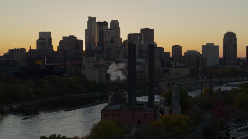 5.7K stock footage aerial video descend by power plant at sunset with view of skyline of Downtown Minneapolis, Minnesota Aerial Stock Footage | DX0001_002542