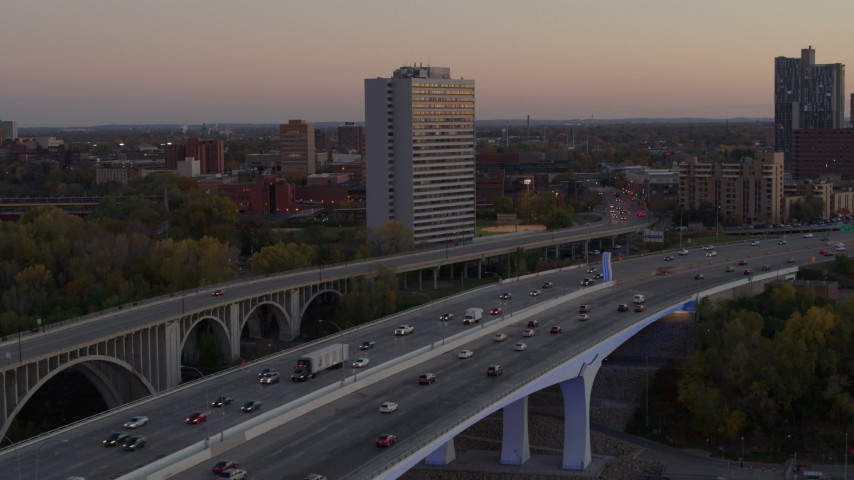 5.7K stock footage aerial video of cars crossing a bridge near condo complex at sunset, Minneapolis, Minnesota Aerial Stock Footage | DX0001_002547