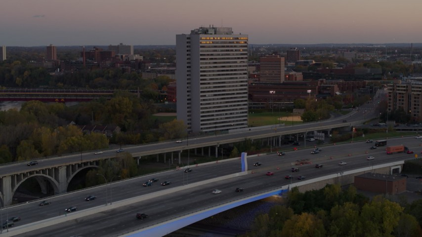 5.7K stock footage aerial video of a condo complex seen from a bridge at sunset, Minneapolis, Minnesota Aerial Stock Footage | DX0001_002548